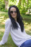 Stock Photo of Brunette in sunglass sitting on green grass