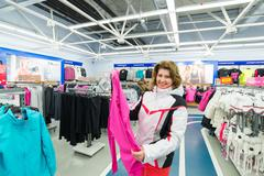 Middle-aged woman chooses clothes in  sports shop Stock Photos