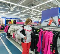 middle-aged woman chooses clothes in  sports shop - stock photo