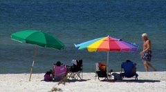 People lounging under colorful beach umbrellas and walking Stock Footage