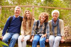 Grandparents and teens sitting on a bridge in a forest - stock photo