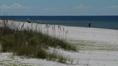 person walks down white sandy beach, sea oats in foreground, water bkg Stock Footage