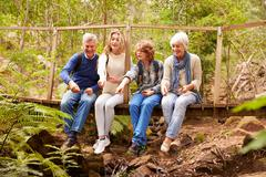 Grandparents and teens playing on a bridge in a forest - stock photo