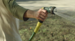 Closeup guy hand watering  garden grass with plastic hose Stock Footage