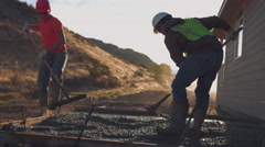 Two concrete workers raking concrete at sunrise - stock footage