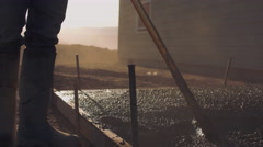 Closeup of worker raking newly poured concrete Stock Footage