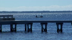 boat with 2 people silhouetted on blue sparkling water, - stock footage