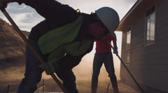 Cinematic silouhettes of workers in hard hats spreading concrete  Stock Footage