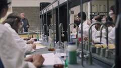 A science professor teaches his students from the front of the classroom - stock footage