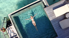 AERIAL: Beautiful woman floating on water surface in villa pool Stock Footage