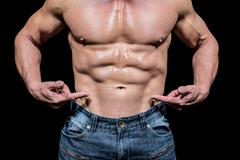Midsection of shirtless man pointing at abs Stock Photos