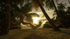 Young woman swinging in hammock at beautiful sunset on beach - stock footage