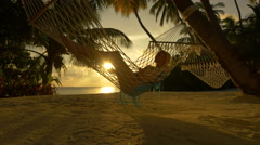Young lady lying in hammock, enjoying tropical vacation in paradise - stock footage