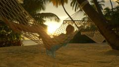Beautiful young blonde woman relaxing in hammock on exotic beach - stock footage