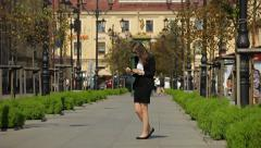 Young woman dressed in a business suit using her digital tablet on a street. Stock Footage