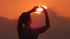 Young woman makes hearts with her hands over the sun Stock Footage