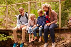 Happy family playing on a bridge in a forest, full length Stock Photos