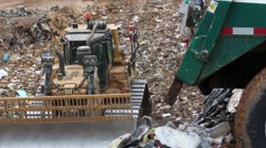 Trash Dropping from Truck While Dozer Pushes it Aside Stock Footage