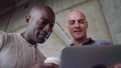 4K Happy male friends laughing and looking at computer tablet outdoors in city Stock Footage