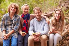 Parents and teenage kids eating outdoors in a forest, portrait Stock Photos