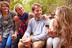 Parents and teenage kids eating outdoors in a forest Stock Photos