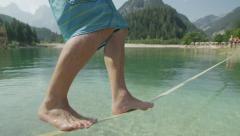 SLOW MOTION: Man slacklining and falling into the lake Stock Footage