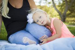 Beautiful Young Blue Eyed Girl Resting on Her Mommy's Lap Outside At the Park - stock photo