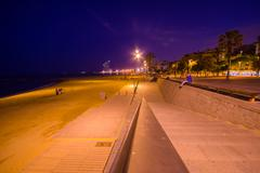 Beautiful Barcelona beach avenue at night in a charming dusky yellow light and - stock photo