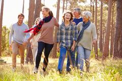 Multi-generation family with teens walking in countryside - stock photo
