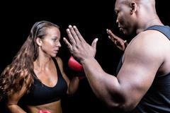 Stock Photo of Trainer instructing female boxer
