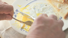 Man cutting up fried egg yolks Stock Footage