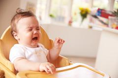 Unhappy Baby In High Chair At Meal Time - stock photo