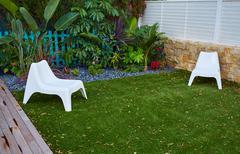 Tropical garden with artificial grass turf wood deck Stock Photos