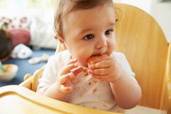 Happy Baby In High Chair At Meal Time - stock photo