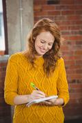 Smiling woman writing on spiral notebook Stock Photos