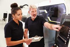 Female Apprentice Working With Engineer On CNC Machinery - stock photo