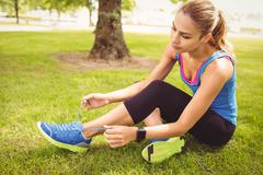 Woman tying shoelace at park Stock Photos