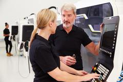 Two Engineers Operating CNC Machinery On Factory Floor - stock photo