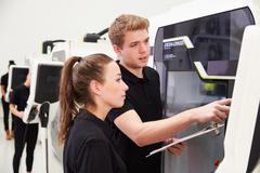 Two Young Engineers Operating CNC Machinery On Factory Floor - stock photo