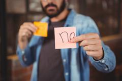 Close-up of man showing adhesive note Stock Photos