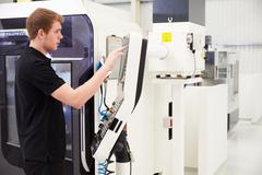 Male Engineer Operating CNC Machinery On Factory Floor - stock photo