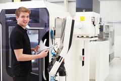 Portrait Of Male Engineer Operating CNC Machinery In Factory Stock Photos