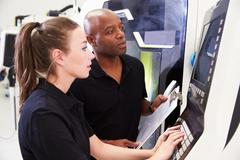Female Apprentice Working With Engineer On CNC Machinery Stock Photos