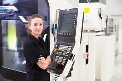 Portrait Of Female Engineer Operating CNC Machinery Stock Photos