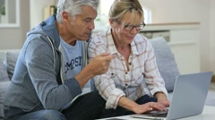 Senior couple at home websurfing on laptop computer - stock footage