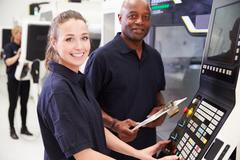 Portrait Of Apprentice Working With Engineer On CNC Machine Stock Photos