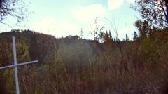 Cross in feild field outside forest Stock Footage