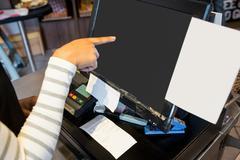 Waitress using touchscreen at till Stock Photos
