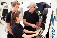 Two Apprentices Working With Engineer On CNC Machinery - stock photo