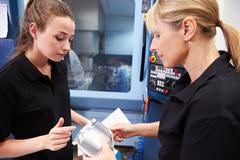 Apprentice Working With Female Engineer On CNC Machinery - stock photo